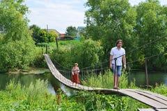 La gente cammina sul ponte sospeso sopra il fiume Fotografie Stock Libere da Diritti