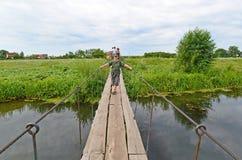 La gente cammina sul ponte sospeso sopra il fiume Fotografia Stock