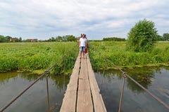 La gente cammina sul ponte sospeso sopra il fiume Immagine Stock Libera da Diritti