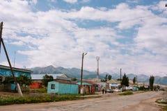 La gente cammina tramite la via di piccola città centroasiatica con il fondo delle montagne Fotografie Stock