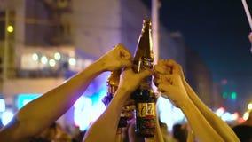 La gente celebra la victoria y golpea las botellas de cerveza sobre sus cabezas