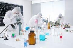 La gente che analizza le reazioni chimiche in un laboratorio Fotografie Stock Libere da Diritti