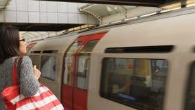 La gente che aspetta al binario sotterraneo del tubo un treno per arrivare nella stazione della metropolitana di Hammersmith Lond archivi video