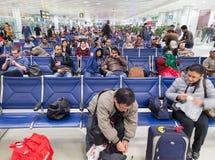 La gente che aspetta il loro volo all'aeroporto internazionale di Doha Immagine Stock