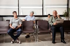 La gente che aspetta nell'ingresso dell'ospedale Immagini Stock