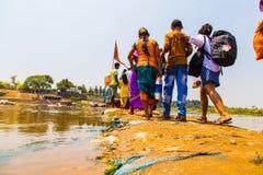 La gente che attraversa fiume indiano, Hampi Immagini Stock