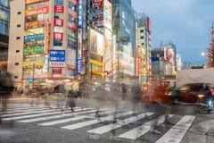 La gente che attraversa una via in una zona commerciale a Tokyo immagini stock libere da diritti