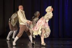 La gente che balla in costumi tradizionali in scena, Immagine Stock