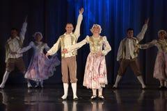 La gente che balla in costumi tradizionali in scena, Immagini Stock