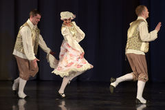 La gente che balla in costumi tradizionali in scena, Fotografie Stock