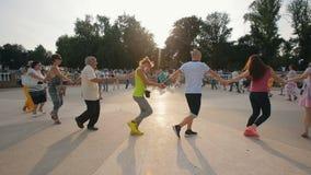 La gente che balla in un tenersi per mano del cerchio stock footage
