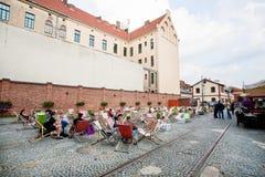 La gente che beve e che si siede nei lettini del caffè della via nel vecchio deposito del tram Immagini Stock Libere da Diritti