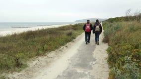 La gente che cammina avanti alla passeggiata della spiaggia dell'isola Germania di Hiddensee stock footage
