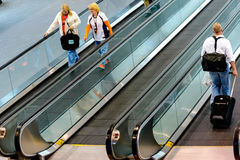 La gente che cammina con i bagagli in aeroporto Immagine Stock