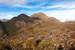 La gente che cammina con i grandi zainhi nel paesaggio della montagna - trekking che fa un'escursione mountaneering nella gamma B immagini stock libere da diritti