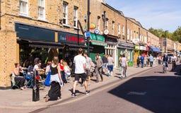 La gente che cammina davanti ai negozi ed ai ristoranti del locale nel mercato di Broadway, Londra orientale Immagini Stock