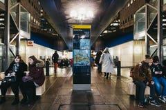 La gente che cammina dentro la stazione ferroviaria leggera dei Docklands di Canary Wharf, Londra, Regno Unito fotografie stock libere da diritti
