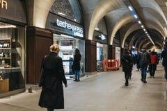 La gente che cammina dopo i negozi dentro la stazione di ferrovia del ponte di Londra, Londra, Regno Unito fotografia stock