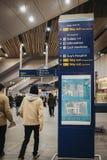 La gente che cammina dopo il segno direzionale dentro la stazione di ferrovia del ponte di Londra, Londra, Regno Unito immagine stock