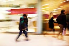 La gente che cammina dopo l'esposizione della finestra nel negozio di vestiti Fotografia Stock