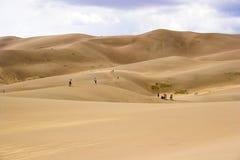 La gente che cammina in dune di sabbia Immagini Stock