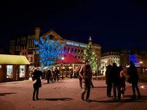 La gente che cammina intorno al mercato di Natale a Riga alla notte Fotografie Stock Libere da Diritti