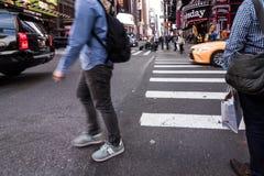 La gente che cammina intorno alle costruzioni in New York, twillight del Times Square Fotografia Stock