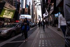 La gente che cammina intorno alle costruzioni in New York, twillight del Times Square Immagine Stock