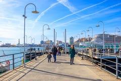 La gente che cammina lungo i pilastri del porto antico a Genova, Italia immagini stock libere da diritti