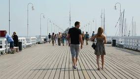 La gente che cammina lungo il pilastro, esaminando le barche attraccate e centro balneare pieno d'ammirazione archivi video