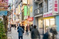 La gente che cammina lungo un marciapiede in una zona commerciale a Tokyo centrale fotografia stock libera da diritti