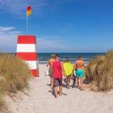 La gente che cammina nella sabbia verso il mare e un rescuetower fotografia stock libera da diritti
