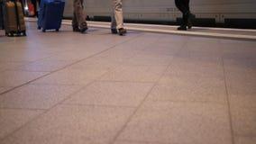 La gente che cammina nella stazione ferroviaria con i bagagli del bagaglio che vanno sul viaggio o sul viaggio di affari stock footage