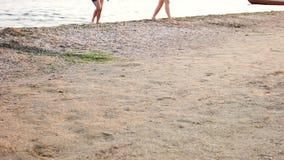 La gente che cammina sulla sabbia della spiaggia archivi video