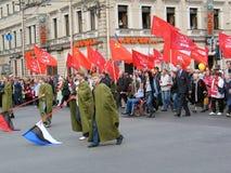 La gente che cammina sulla via con le bandiere Immagine Stock