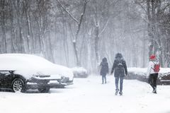 La gente che cammina tramite la via della città coperta di neve durante le precipitazioni nevose pesanti Bufera di neve in città  immagini stock