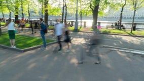 La gente che cammina in un parco Moto panoramico del timelapse archivi video