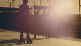 La gente che camminano e biciclette di giro alla siluetta di tramonto archivi video