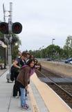 La gente che cerca arrivo del treno Fotografie Stock