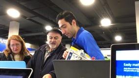 La gente che chiede al lavoratore riguardo al nuovo computer portatile dentro il deposito di Best Buy stock footage