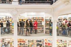 La gente che compera per i libri in biblioteca Immagini Stock Libere da Diritti