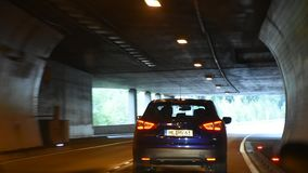 La gente che conduce l'automobile sulla strada passata a montagna in tunnel dell'automobile va in Italia archivi video