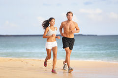 La gente che corre - coppie giovani che pareggiano sulla spiaggia Fotografia Stock