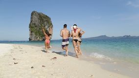 La gente che corre lungo i turisti del gruppo di retrovisione della parte posteriore della spiaggia, dell'uomo e della donna sull archivi video