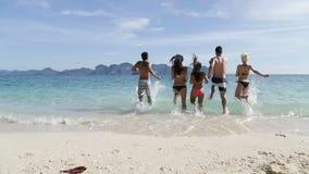 La gente che corre nella retrovisione della parte posteriore di acqua, nel giovane e nel gruppo della donna sulla spiaggia stock footage