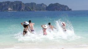 La gente che corre nella ritenzione di acqua passa a spiaggia gli amici posteriori del gruppo di retrovisione, dell'uomo e della  archivi video