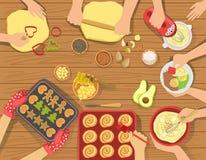 La gente che cucina la pasticceria e l'altro alimento osserva insieme da sopra Fotografia Stock