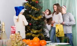 La gente che decora l'albero di Natale Immagine Stock