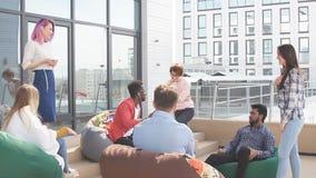 La gente che discute lavorando processo mentre sedendosi al salotto dell'ufficio all'aperto video d archivio