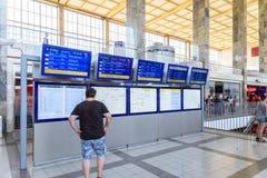La gente che esamina gli schermi di arrivi e di partenza Immagini Stock Libere da Diritti